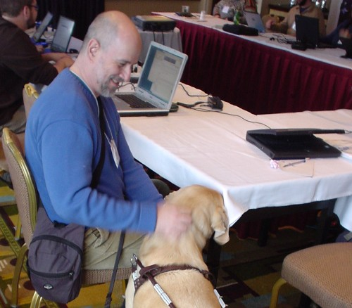 Man in blue sweater sits at table with laptop computer and pats tawny Labrador retriever