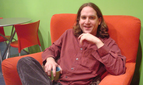 Long-haired young man sits on bright-red chair