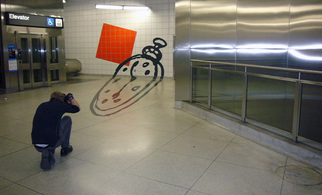 Man crouches to photograph a clock illustrated at angles on subway wall and floor