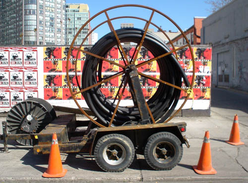 Large spool of thick black cable sits on sidewalk surrounded by orange pylons, almost obscuring a wall behind it sniped with 'Kamataki' posters
