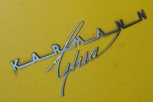 Silver metal script reads 'Karmann Ghia' on puce-yellow metal
