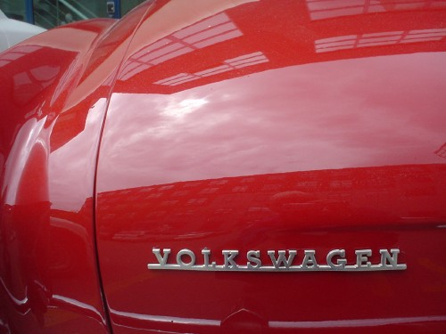 Left rear of red Karmann Ghia shows silver metal Volkswagen nameplate