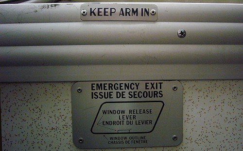 Two plaques attached to wall read KEEP ARM IN and EMERGENCY EXIT (with diagram of trapezoidal window)