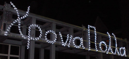 Sign made of Christmas bulbs reads Χρονιαπολλα with a misshapen π