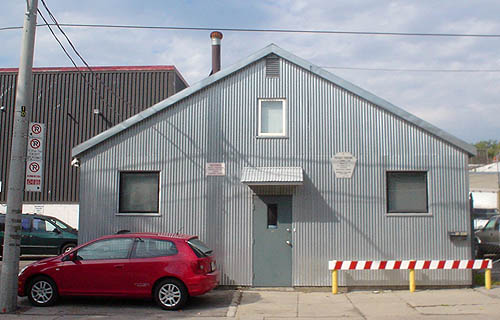 Silver corrugated metal A-frame building has red-and-white-striped fence along the front, with red two-door car parked at the left