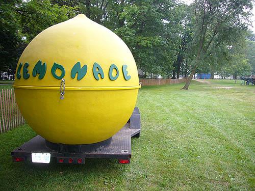 Giant sculpture of a lemon sits on a trailer on a grass field. Legend: LEMONADE