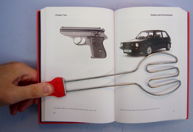 Red-handled steel tongs hold a book open showing a Walther PPK pistol and Golf GTI, both black with tiny red accents