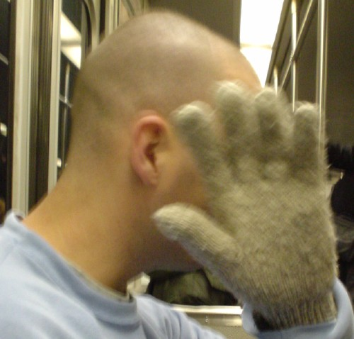 Shaven-headed man holds a gloved hand in front of his face in one photo and turns away from the camera in another