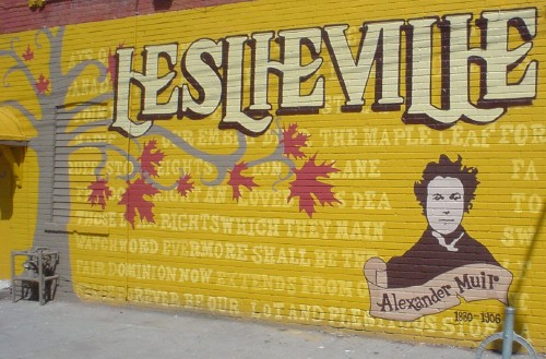 Yellow wall mural reads LESLIEVILLE and shows many lines of text, a maple tree, and a likeness of Alexander Muir