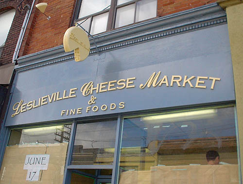 Blue sign has yellow lettering reading LESLIEVILLE CHEESE MARKET & FINE FOODS in a bank gothic with script initial letters