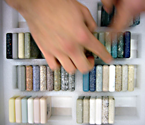 Hands hover over a foam display case of speckled, beige, and tan Corian samples