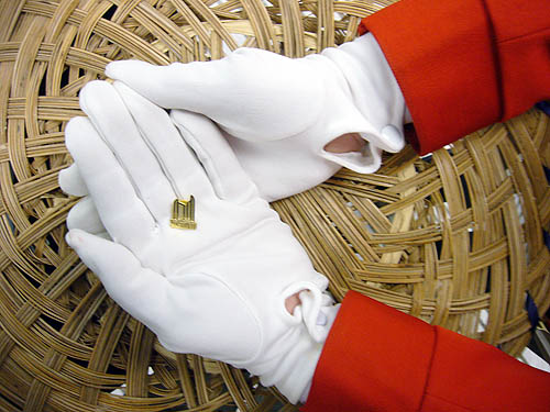 White-gloved hands extending from red-serge sleeves hold a tiny brass lapel pin in the shape of Toronto City Hall