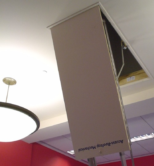 Trap door descends from ceiling with attached ladder sides. Label reads: Access-Rooftop Mechanical