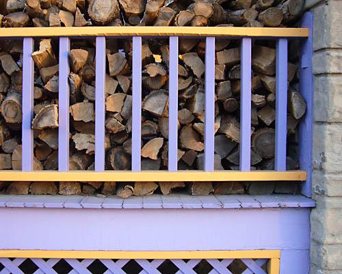 Logs piled behind purplish-blue and yellow slats of a porch railing