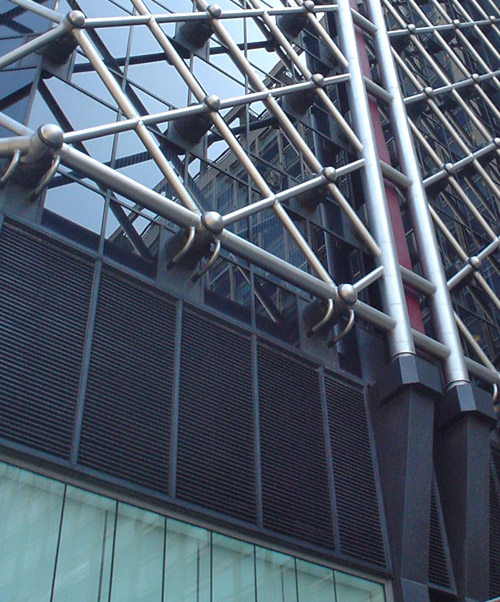 Glass-walled skyscraper is covered with a lattice of metal tubing like a chain-link fence
