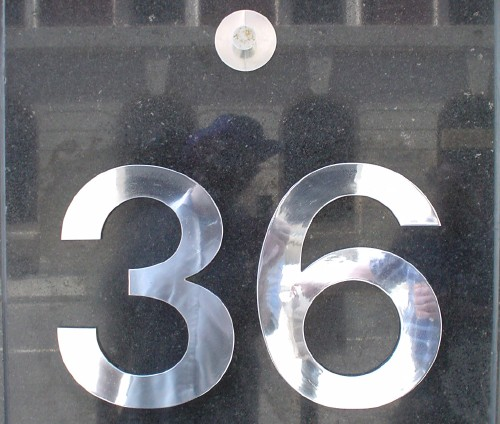 Silver metal letters in Helvetica read 36 attached to granite slab. A silver peg is attached above the numbers