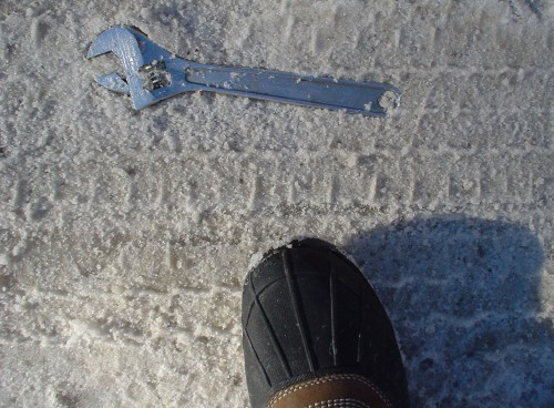 Toe of boot protrudes into frame showing ordinary wrench embedded flush into snow