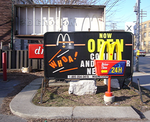 A plethora of overlapping and/or broken McDonald's signs all grouped together