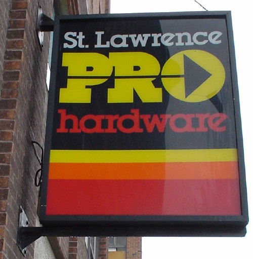 Black-and-orange sign reads 'St. Lawrence Pro Hardware' in Lubalin font, with diagonal-crossbar letter 'e'