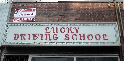 Sign on brick building reads LUCKY DRIVING SCHOOL in script typeface with mismatched stroke thicknesses and angles