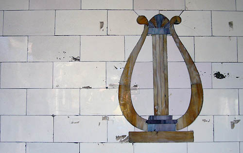 Cracked tiles on wall are painted with a lute (solid base, central column, two arms at sides that curve upward and finish in knobs at the top of the column)