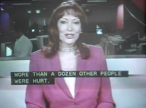 Raven-haired woman in low-cut red blazer (also with visible captions)