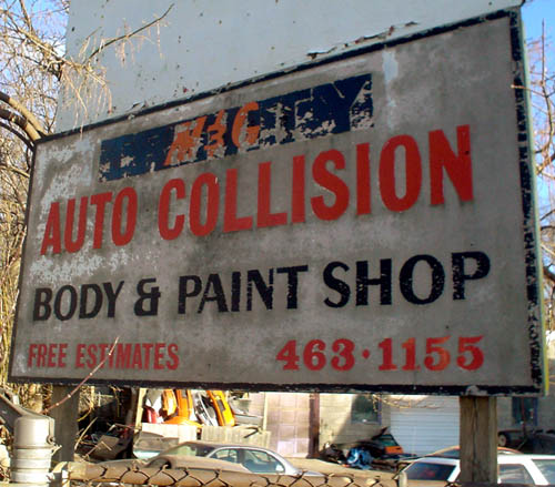Severely weathered sign reads M&C AUTO COLLISION BODY & PAINT SHOP FREE ESTIMATES