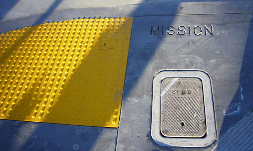 Alongside a nubbly yellow edge marker, concrete in a sidewalk is embossed MISSION