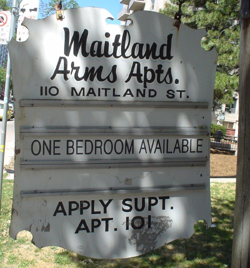 Carved sign in the shape of a shield reads Maitland Arms Apts.  in script, with hand-lettered 110 MAITLAND ST. and Helvetica Condensed insert reading ONE BEDROOM AVAILABLE
