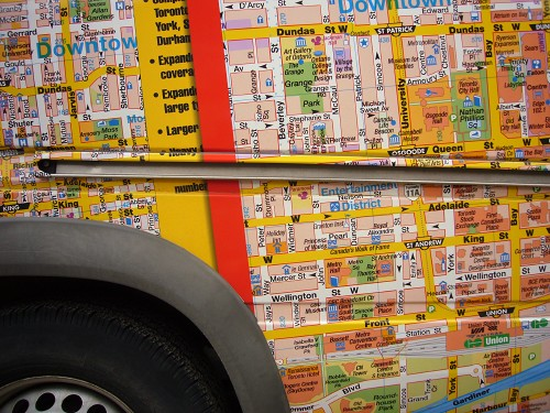 Vehicle covered with map of downtown Toronto, broken up by a channel for a sliding door and a top corner of fender and wheel