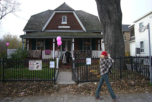Woman walks by Maple Cottage, decorated with balloons and a few small signs