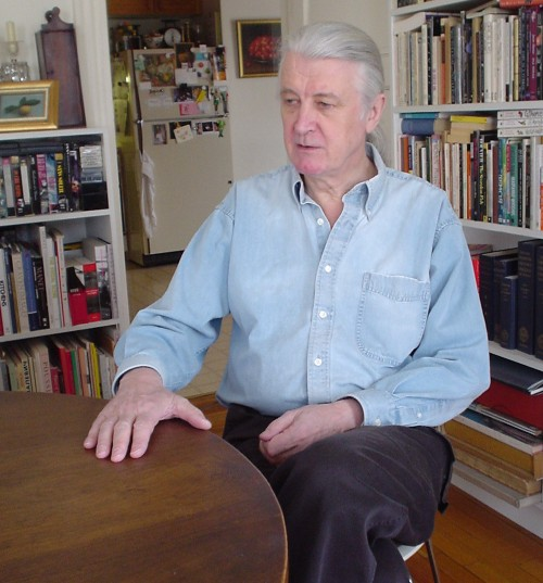 Distinguished gentleman with grey hair in a ponytail sits in a book-lined room