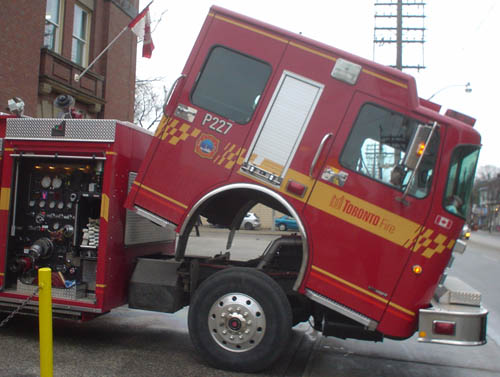 Red Toronto fire engine's cab rotates away from the wheels along the axis of the front bumper, with an open service panel on the main body behind it