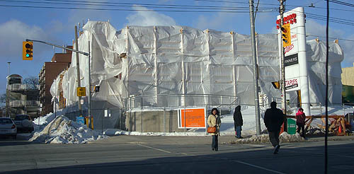 Building under construction shrouded in billowy white panels