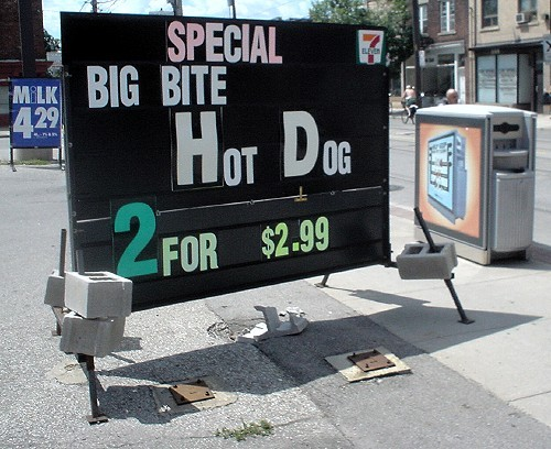 Four-foot-high billboard with garbage receptacle on the edge sits at curb, while movable 7-Eleven sign, held down by bricks, reads SPECIAL BIG BITE HOT DOG 2 FOR $2.99