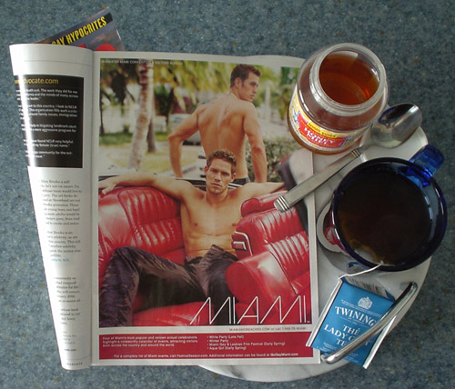 Magazine ad (next to blue teacup and honey jar) shows shirtless man lounging in red-upholstered convertible with the legend MIAMI