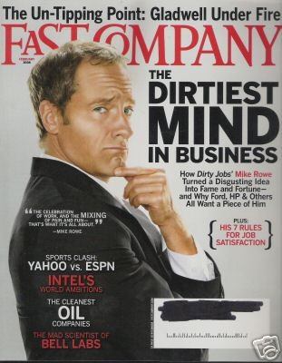 Mike Rowe, dressed in a suit, presses his chin and looks bemused