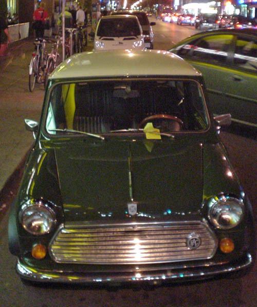 Green Ausin Mini parked in front of white Smart at night (with other car backing in between them)