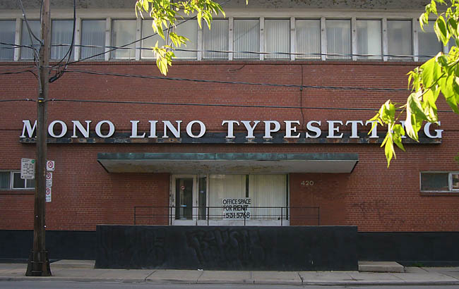 Behind a few green-leafed branhes, a hulking building has a sign reading MONO LINO TYPESETTING