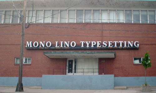 Red brick building has row of windows across its entire third floor and MONO LINO TYPESETTING in metal Plantin type over the raised front entrance