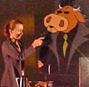 Giant cutout of bull in a black duster speaks into microphone onstage