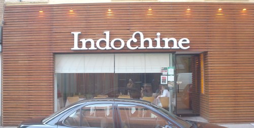 Sign above wood-paneled front of restaurant reads Indochine in Mrs Eaves, complete with ch ligature