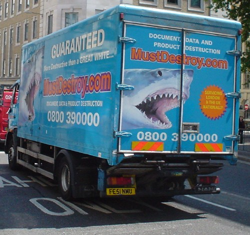 Ocean-blue delivery truck features a shark about to bite and the legend MustDestroy.com DOCUMENT, DATA AND PRODUCT DESTRUCTION