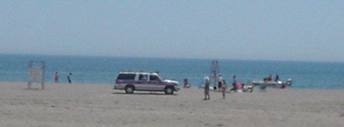 White Suburban with red and blue stripes sits alongside a few people on a distant beach