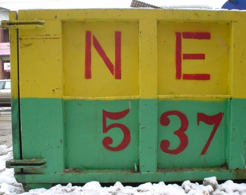 Yellow-and-green dumpster is painted with 'NE' and '537' in red
