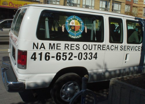 Van is labeled NA ME RES OUTREACH SERVICES in Arial (with phone number in Helvetica Condensed)