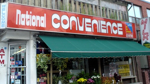 Orange sign reads National CONVENIENCE in curvy white letters whose thick strokes contrast severely with thin strokes