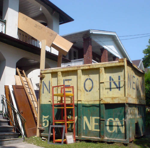 Dumpster on lawn outside of house reads NEON in green letters on the yellow upper half and yellow letters on the green lower half