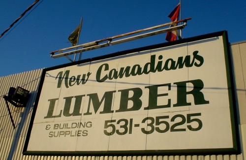 At dusk, hand-drawn sign on building wall reads New Canadians LUMBER & BUILDING SUPPLIES 531-3525