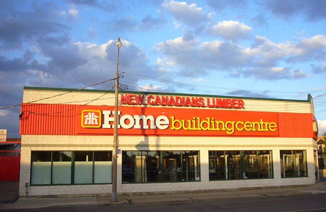 Late-dusk sunshine illuminates an orange New Canadians Lumber Home Building Centre sign, most of it typeset in Lubalin Graph